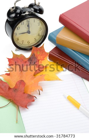 "Pile of books, writing-book, pen, alarm clock and autumn leaves on a white background. Concept for ""Back to school"""