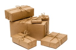 Pile of boxes wrapped with brown kraft paper and tied with twine on a white background. Delivery, moving, gifts concept