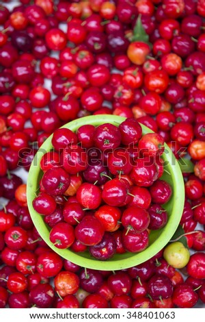 Pile of bright red acerola cherries stacked on display at an outdoor fruit and vegetable market in Rio de Janeiro, Brazil - stock photo