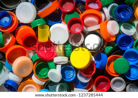 Pile of brightly colored plastic bottle tops gathered on the beach to highlight the crisis of worldwide ocean pollution #1237285444