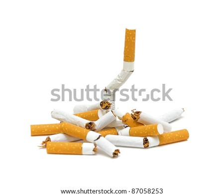 Pile of broken cigarettes closeup on white background. No smoking.