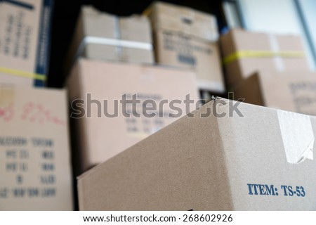 Pile of brown cardboard boxes at warehouse of market. Different stuff packed in carton boxes. Moving concept. Set of cargo boxes ready for delivery.