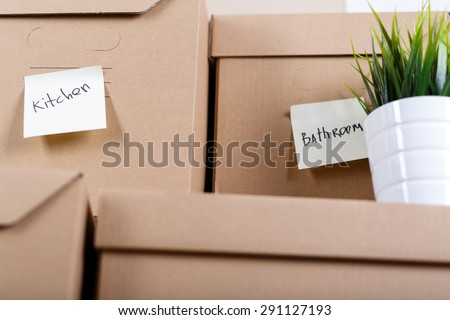 Pile of brown cardboard boxes with house or office goods. Different stuff packed in carton boxes. Moving concept. Set of cargo boxes with yellow sticker labels ready for transportation and unpacking