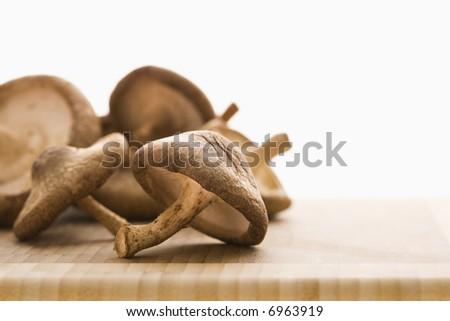 Pile of brown mushrooms on cutting board.