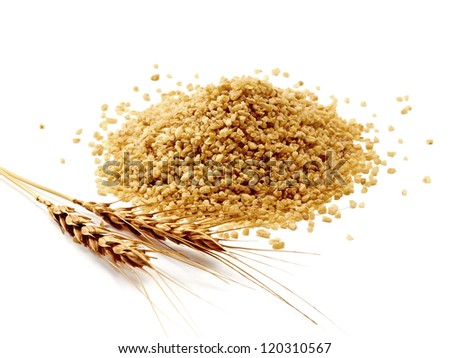 Pile of bulghur (couscous) with wheat ears on white background