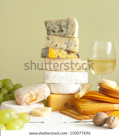 Pile of cheese many various types with wine grapes and walnuts