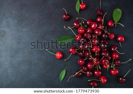 Pile of cherry with leaf and water drops on black stone table. Ripe ripe cherries. Sweet red cherries. Top view. Rustic style. Fruit Background