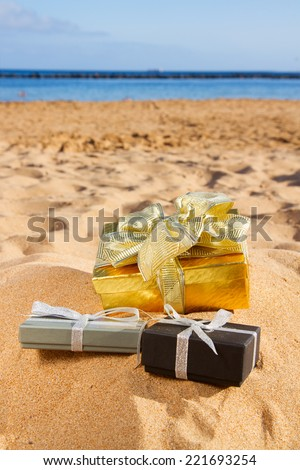 pile of christmas gifts on beach  with golden sand at sunny day