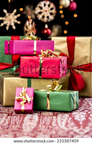 Pile of Christmas gifts wrapped in red, gold, green and magenta. Shallow depth of field. blurred stars, baubles and twinkles in the back. Xmas background with text space.