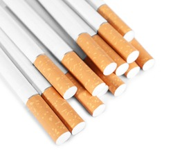 Pile of cigarettes with orange filters on white background, above view