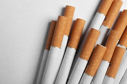 Pile of cigarettes with orange filters on white background, flat lay