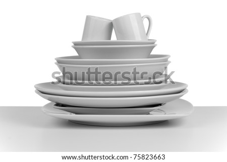 Pile of clean empty dishes and cups on white background. - stock photo