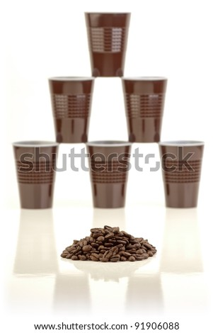 Pile of coffee beans and a stack of plastic cups arranged in the background on white.