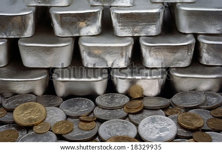Pile of coins from around the world and bars of silver