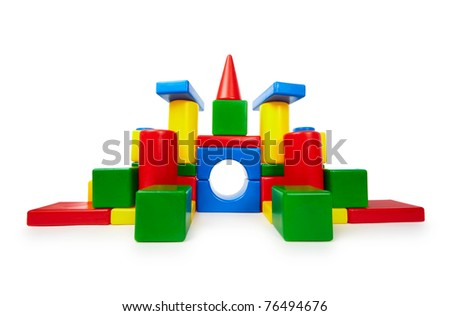 Pile of colored toy bricks like a castle on white