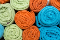 Pile of colorful blankets made from fleece, all rolled up.