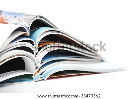 pile of colorful opened magazines on white background