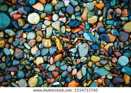 Pile of colorful Sea Pebble stones and rocks on beach.Different forms multicolor Pebbles (orange,white,yellow,blue,green,red) as natural abstract texture background.Close up colourful Pebbles on coast - Shutterstock ID 1154715760