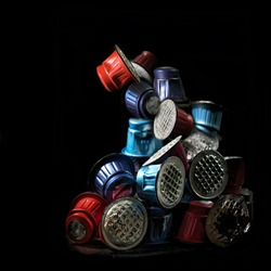 Pile of colorful used coffee capsules against a black background, unnecessary waste from disposable packaging, art concept for environmental protection, copy space, selected focus