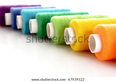 Pile of coloured bobbins of lurex thread isolated on white - stock photo