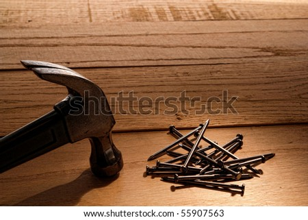 Pile of common nails and carpenter claw hammer tool on wood boards work bench in a carpentry construction workshop