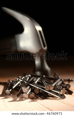 Pile of common nails and steel claw carpentry hammer at a construction work site
