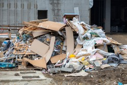 Pile of construction waste in front of an unfinished building.