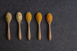 Pile of corn grit on wooden spoon place of black velvet