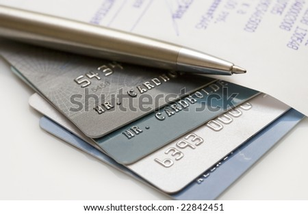 Pile of credit cards with pen and bill. Narrow focus