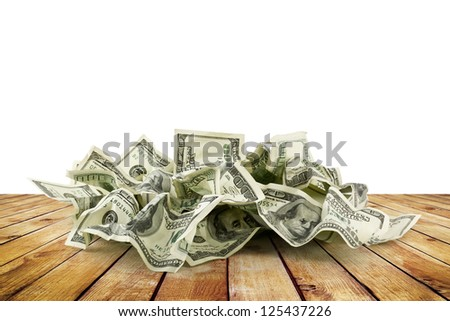 Pile of crumpled money dollar bills on wood planks overs white background