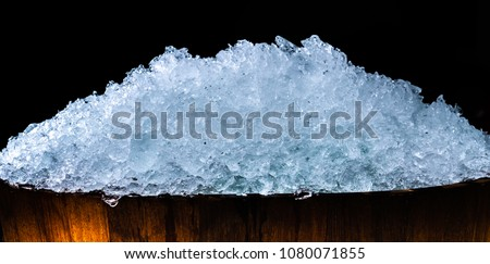Pile of crushed ice cubes in wood bucket on dark background with copy space. Crushed ice cubes foreground for beverages, beer, whisky, fruit juice, milk, fresh food or fresh vegetables.