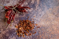 Pile of crushed red pepper, Cayenne pepper, dried chilli on a motley background. Next to a bunch of whole dry chili peppers. It is a popular spicy condiment for Mexican dishes. Copy space.