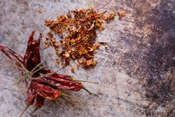 Pile of crushed red pepper, Cayenne pepper, dried chilli on a motley background. Next to a bunch of whole dry chili peppers. It is a popular spicy condiment for Mexican dishes. Top view. Copy space.