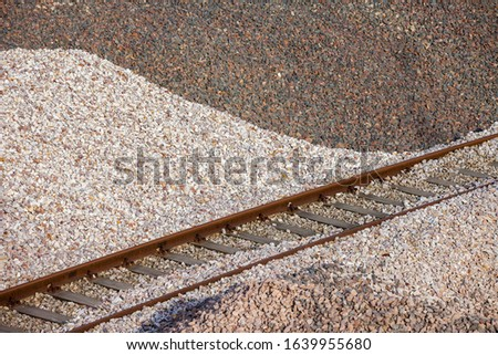 Pile of crushed stones used as ballast in the rail industry with railway track