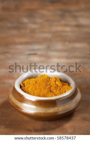 pile of Curry powder in a pot on old wooden background, shallow DOF