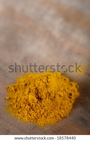 pile of Curry powder on old wooden background, shallow DOF