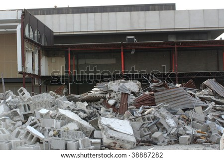 Pile of debris in front of a partially demolished building.