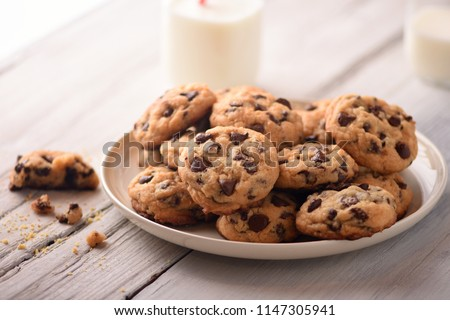 Pile of Delicious Chocolate Chip Cookies on a White Plate with Milk Bottles
