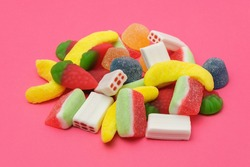 Pile of delicious colorful, tasty candies of different shapes on a pink background.