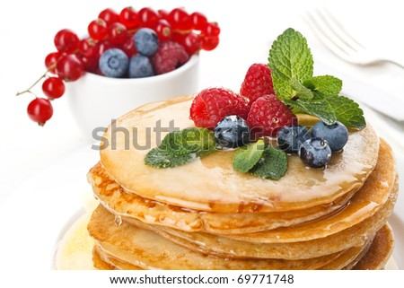 Pile of delicious handmade pancakes topped with honey, raspberries and bilberries on feast table