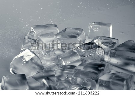 pile of different ice cubes on reflection table with water drop, on misted light grey surface
