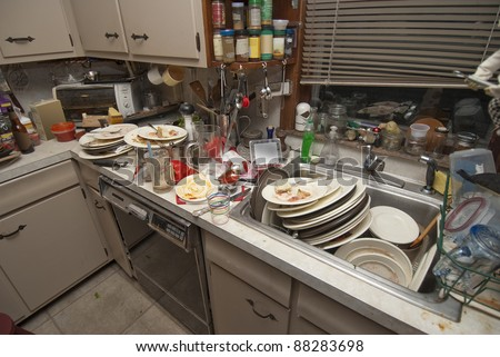 Pile of dirty dishes in sink and counter top after a party