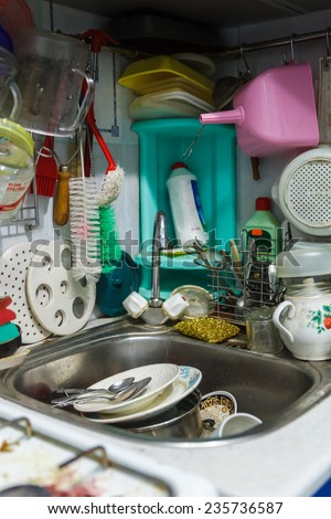 Pile of dirty dishes in sink and counter top, mess in the kitchen