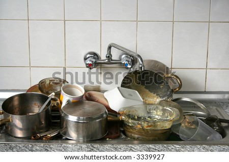 Pile of dirty dishes in the metal sink
