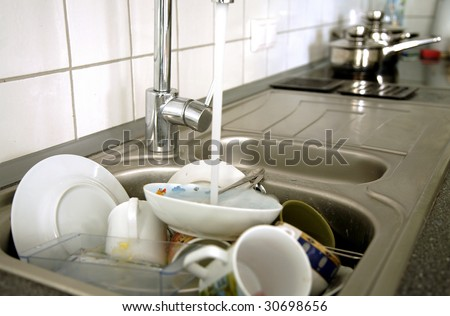 Pile of dirty dishes in the metal sink and pouring tap water. Kitchen after breakfast.
