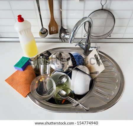 Pile of dirty dishes in the sink stainless steel