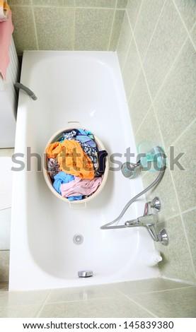 Pile of dirty laundry in bath washing machine green bathroom