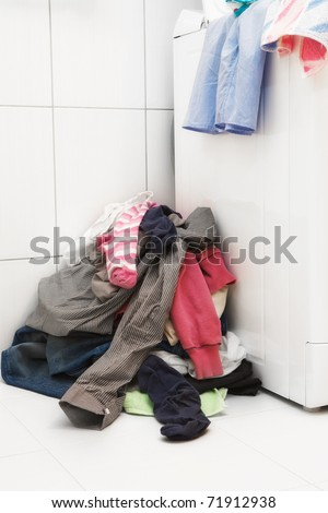 Pile of dirty laundry next to washing machine