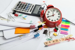 Pile of documents, alarm clock, calc and office stuff - time menegment concept
