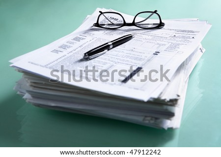 Pile of documents and tax form on the table with glasses and pen. Focus on the glasses